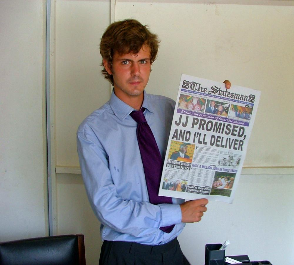 An intern at a journalism placement in Ghana holds up a newspaper